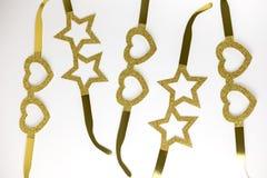 Lentes de oro de la cartulina en la forma de las estrellas y corazones que mienten en una tabla blanca Estilo de Minimalistic Vis Imagen de archivo libre de regalías