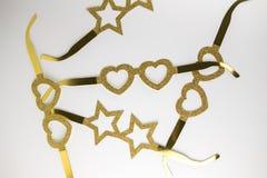 Lentes de oro de la cartulina en la forma de las estrellas y corazones que mienten en una tabla blanca Estilo de Minimalistic Vis Fotos de archivo