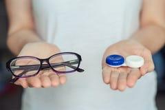 Lentes e vidros de contato da posse da mulher nas mãos conceito da escolha da proteção da visão imagens de stock