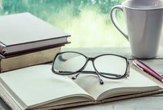 Lentes en el cuaderno abierto con el libro, taza de la pluma y de café Foto de archivo libre de regalías