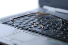 Lentes en el teclado de la computadora portátil Imagen de archivo