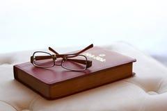 Lentes en la biblia santa con el backlighting Foto de archivo libre de regalías