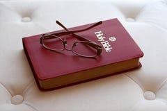 Lentes en la biblia santa con el backlighting Imagen de archivo