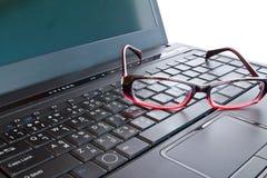 Lentes en la computadora portátil Imagenes de archivo