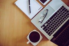 Lentes en pluma del teclado del ordenador portátil en el cuaderno con la taza de café Imagen de archivo libre de regalías