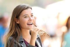 Lentes penetrantes de la muchacha feliz en la calle Imágenes de archivo libres de regalías