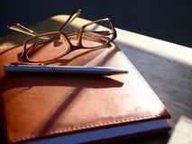 Lentes, pluma y cuaderno Foto de archivo libre de regalías