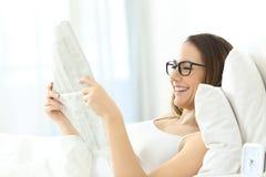 Lentes que llevan de la muchacha que leen un periódico en la cama Fotografía de archivo