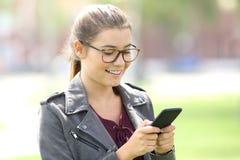 Lentes que llevan de la muchacha que mandan un SMS en un teléfono móvil Fotografía de archivo