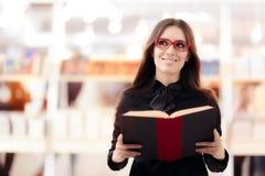 Lentes que llevan sonrientes de la muchacha que hacen compras para los libros Fotografía de archivo libre de regalías