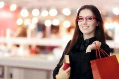 Lentes que llevan sonrientes de la muchacha que hacen compras para los libros Foto de archivo