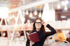Lentes que llevan sonrientes de la muchacha que hacen compras para los libros Foto de archivo libre de regalías