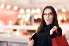 Lentes que llevan sorprendidas de la muchacha que hacen compras para los libros Fotos de archivo libres de regalías