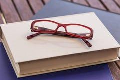 Lentes rojas y libros cerrados Imagen de archivo