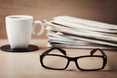 Lentes, taza de café y pila de periódicos en el escritorio de madera para los temas de la oftalmología, visión pobre y lectura Foto de archivo