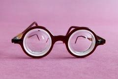 Lentes viejas de las gafas del diseño de la moda en fondo de papel violeta rosado Complementos de los hombres del estilo del vint Fotos de archivo libres de regalías