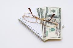 Lentes y billetes de banco de algunos dólares Fotos de archivo libres de regalías