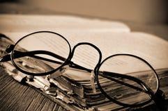 lentes y libro viejo Redondo-enmarcados, en el tono de la sepia fotografía de archivo