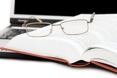 Lentes y libros en la computadora portátil Imagen de archivo libre de regalías