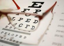Lentes y primer de la carta de ojo en un fondo ligero foto de archivo