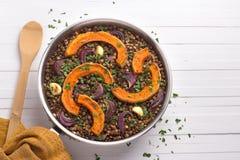 Lenticchie al forno della zucca con le cipolle rosse e l'aglio in una padella Fotografie Stock