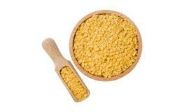 Lenticchie gialle in ciotola di legno e mestolo isolati su fondo bianco nutrizione bio- Ingrediente di alimento naturale fotografia stock libera da diritti