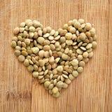 Lenticchie nel cuore sul tagliere di legno del grano, nel formato quadrato per i media, i blog di nutrizione, le insegne e gli am Fotografie Stock Libere da Diritti