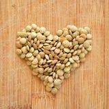 Lenticchie nel cuore sul tagliere di legno del grano, nel formato quadrato per i media, i blog di nutrizione, le insegne e gli am Immagini Stock