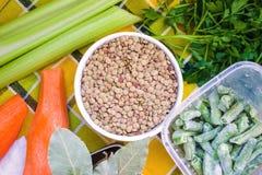 Lenticchie in una tazza circondata dagli alimenti immagine stock