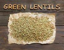 Lenticchie verdi sulla tavola di legno con la parola di legno Fotografie Stock
