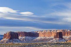 Lenticular clouds over a snow filled Monument Valley. Morning sunrise brightly illuminates Monument Valley's familiar rock formations after an overnight dusting Royalty Free Stock Photography