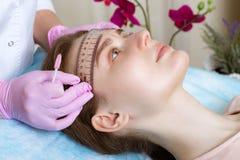 Lentiggini microblasting permanenti di tatuaggio ad una donna in un salone di bellezza fotografia stock