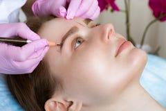 Lentiggini microblasting permanenti di tatuaggio ad una donna in un salone di bellezza fotografie stock libere da diritti