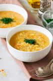 Lentil and bulgur soup puree in a white bowl on a white stone ba royalty free stock photography