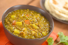 Lentil Curry. Bowl of spicy Indian dal (lentil) curry prepared with carrot and potato, chapati flatbread in the back and cilantro leaf on the side (Selective Royalty Free Stock Photo
