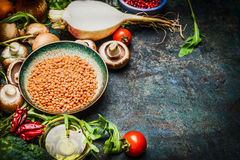 Lentil with fresh vegetables and ingredients for cooking on blue rustic background, close up. Stock Images