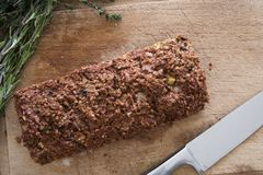 Whole Lentil Loaf on Cutting Board. Lentil loaf on cutting board with herbs and knife, view from above Royalty Free Stock Photography