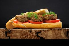 Lentil patty sandwich with tomato and carrot greens in old woode Royalty Free Stock Photography