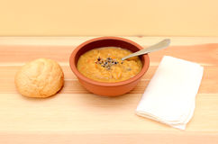 Lentil soup in a bowl with seasoning and bread roll Royalty Free Stock Photos