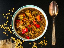 Lentil soup in a round bowl with vintage spoon  on a black table. Lentil soup with carrot, chorizzo pieces in a round bowl with vintage spoon  on a black table Stock Photos