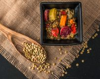 Lentil soup with chorrizo pieces. Colorful lentil soup in a blck ceramic bowl, a wooden spoon with lentil seeds on a rustic table cloth Stock Images