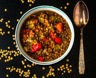 Lentil soup in a round bowl with vintage spoon  on a black table. Lentil soup with carrot, chorizzo pieces in a round bowl with vintage spoon  on a black table Royalty Free Stock Photography