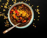 Lentil soup in a round bowl with vintage spoon  on a black table. Lentil soup with carrot, chorizzo pieces in a round bowl with vintage spoon  on a black table Stock Image
