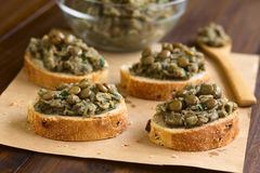 Lentil Spread on Bread. Lentil and parsley spread on bread served on paper, photographed with natural light (Selective Focus, Focus one third into the image Royalty Free Stock Images
