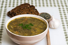 Lentil stew with garlic and bread on white board. Close-up of lentil stew with garlic and bread on white board Stock Photo