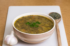 Lentil stew with garlic on white board. Close-up of lentil stew with garlic on white board Royalty Free Stock Image