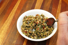 Lentil Tabbouleh Salad. Over a beautiful wooden tray a hand of a person dips into with a spoon a round white dish filled with organic brown lentil with tabouli Stock Images