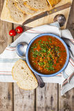Lentil and tomato soup. Served with bread on the stripy cloth over the rustic wooden table Stock Photos