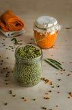 Lentilhas alaranjadas e verdes nos frascos de vidro Imagem de Stock Royalty Free