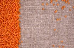 Lentilhas alaranjadas em um fundo de linho Fotos de Stock Royalty Free